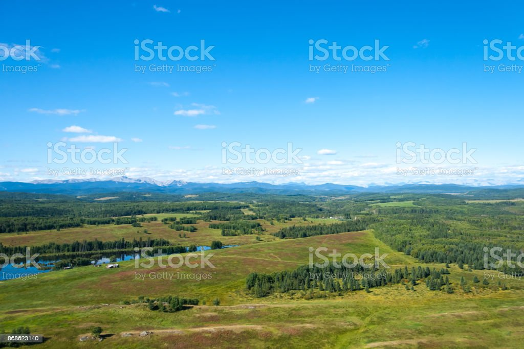 An aerial view of green forest and farm with Rocky Mountains in a distance. stock photo