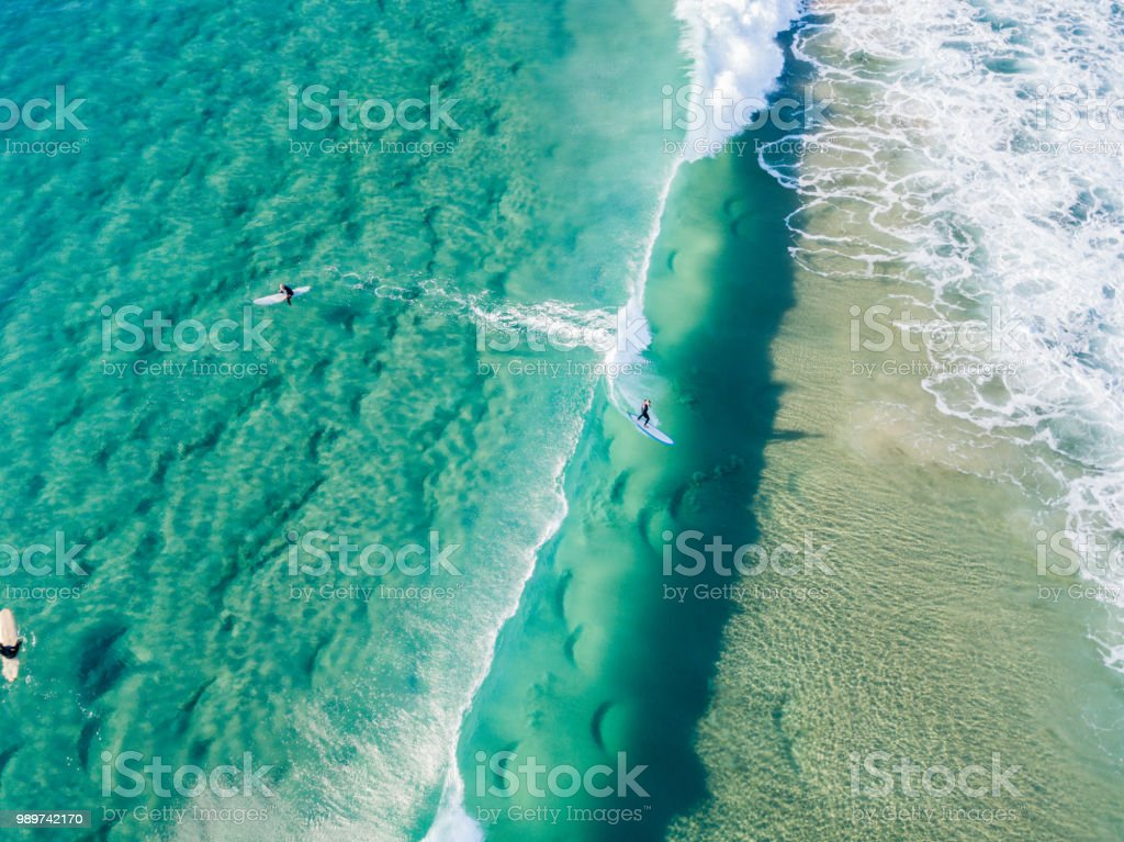 An aerial view of surfers waiting on the surfboard for a wave at the beach royalty-free stock photo