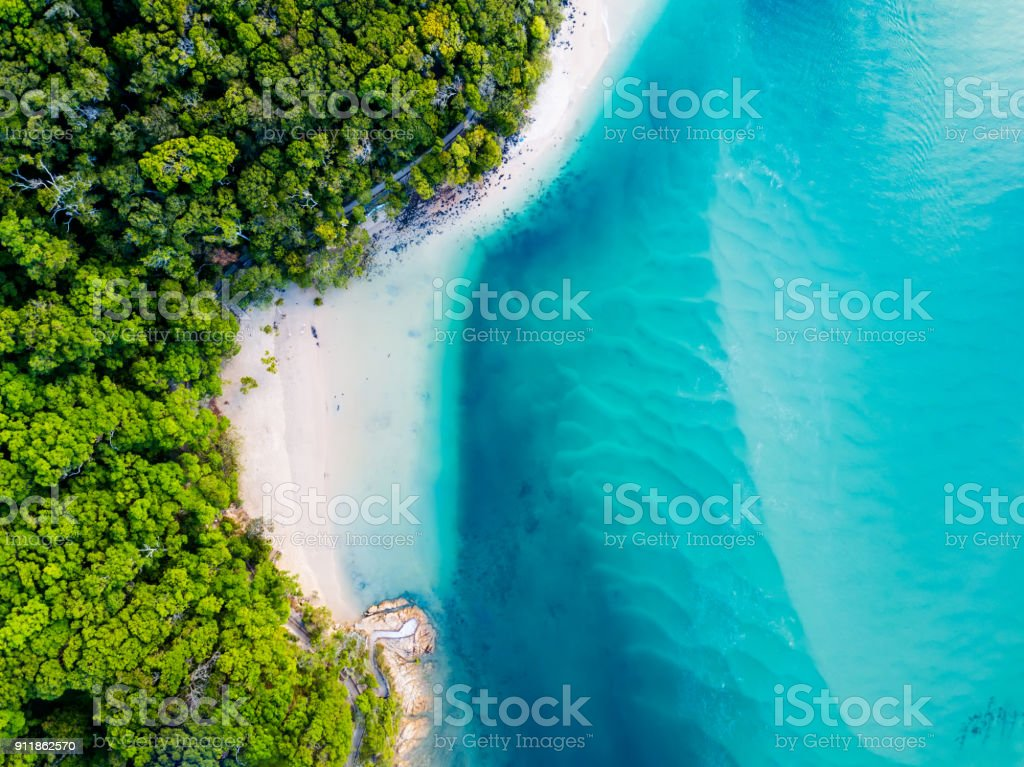 An aerial view of the beach with blue water stock photo