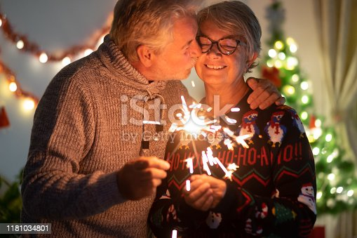 An affectionate kiss between elderly wife and husband who celebrate Christmas with sparks. Lights and Christmas tree in the background