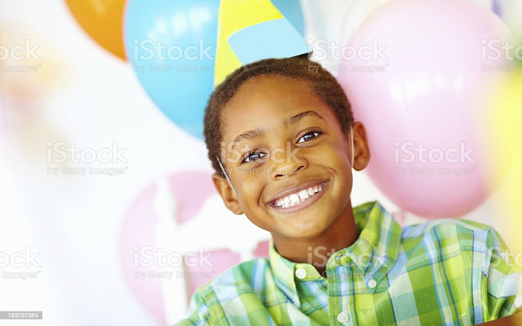 An African American birthday boy with balloons in the background royalty-free stock photo