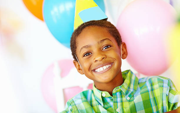 An African American birthday boy with balloons in the background stock photo
