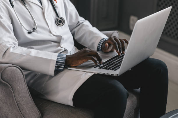 an African American doctor conducts an appointment via a video conference an African American doctor conducts an appointment via a video conference. High quality photo medical technology stock pictures, royalty-free photos & images