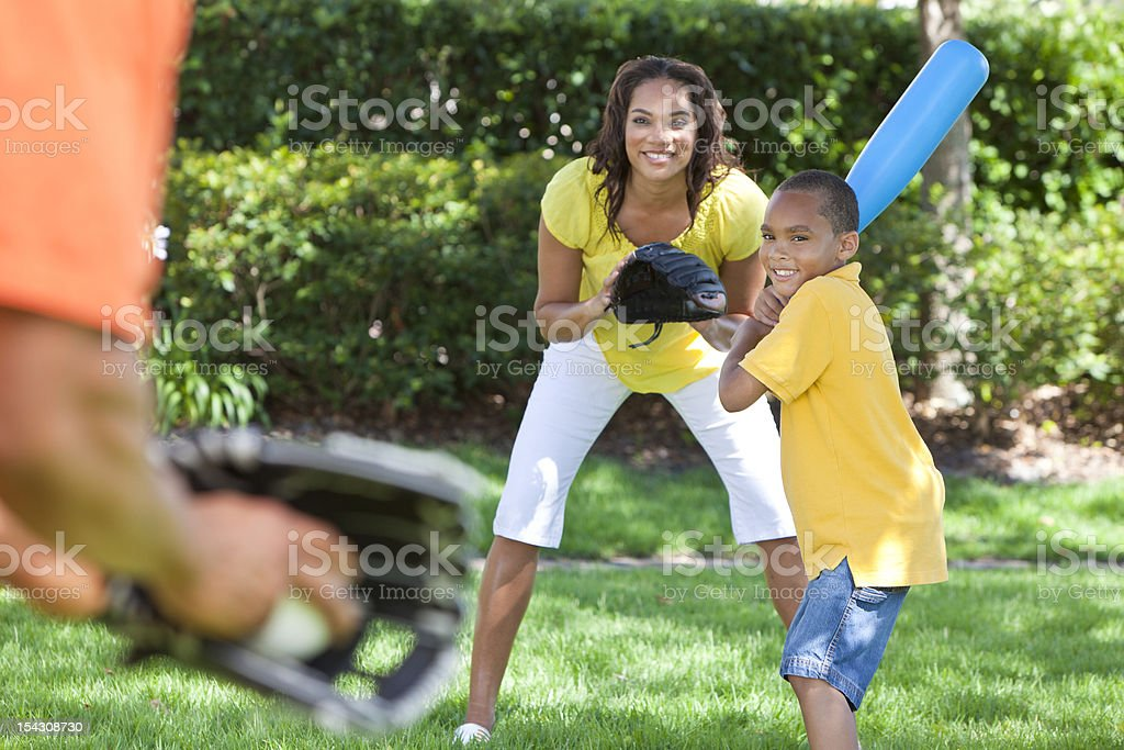 An African American family playing baseball on the yard stock photo