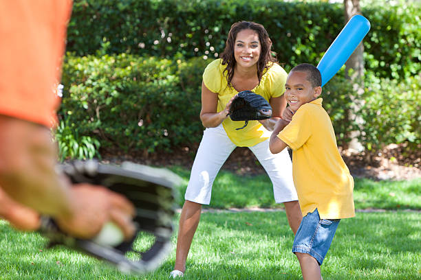 An African American family playing baseball on the yard African American family, man, woman, boy child, mother, father, son playing baseball together outside. baseball sport stock pictures, royalty-free photos & images