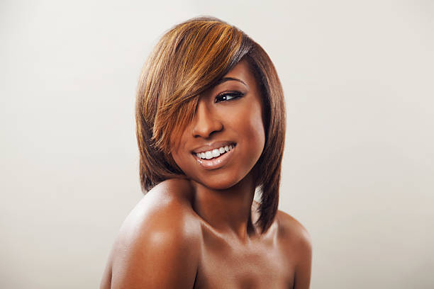 An African American female with caramel highlights smiling Portrait of a young African American woman with a fashionable hairstyle with blonde highlights highlights hair stock pictures, royalty-free photos & images