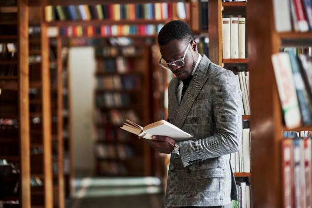Ein afroamerikanischer Mann im Business-Anzug steht in einer Bibliothek im Lesesaal – Foto