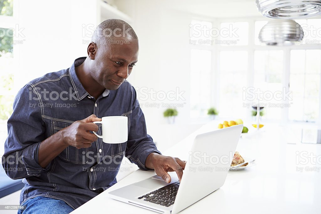 An African American man using his laptop while drinking stock photo