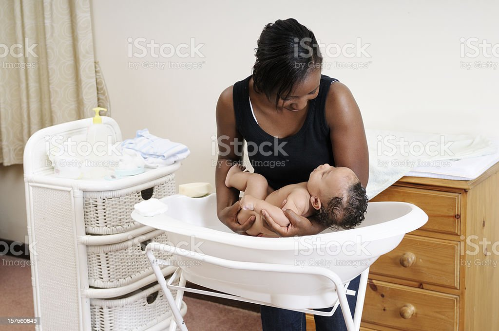 An African American Woman Lowering Baby Into Bath stock photo