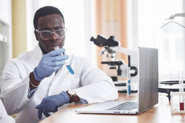 Ein afroamerikanischer Arbeiter arbeitet in einem Labor Experimente. – Foto