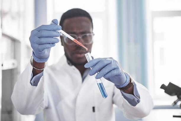 Ein afroamerikanischer Arbeiter arbeitet in einem Labor, das Experimente durchführt. – Foto
