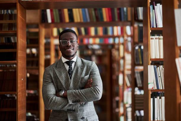 Ein Afroamerikaner Ein afroamerikanischer Mann im Business-Anzug, der in einer Bibliothek im Lesesaal steht. – Foto