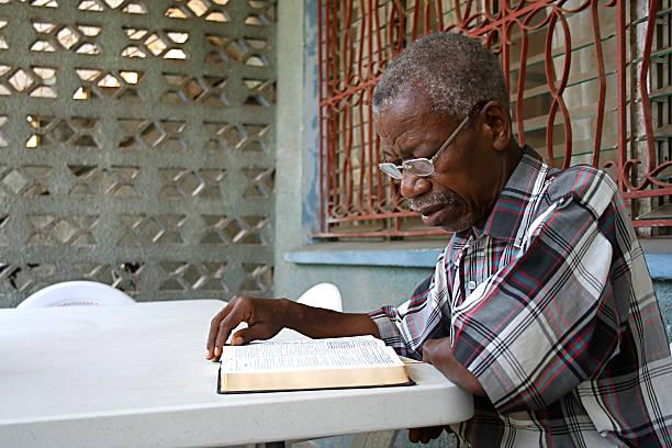 An African elderly gentleman reading a Bible stock photo