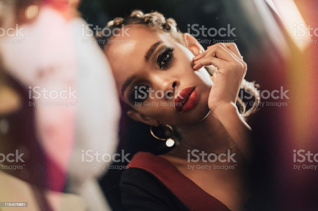 an african female model looking at the mirror with a mask hanging in...