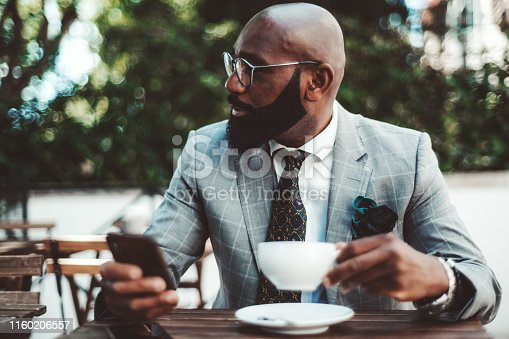 An elegant black bald senior with beard and eyeglasses and in a formal costume is having a coffee break in an outdoor cafe, holding a cup in one hand and his smartphone in another hand