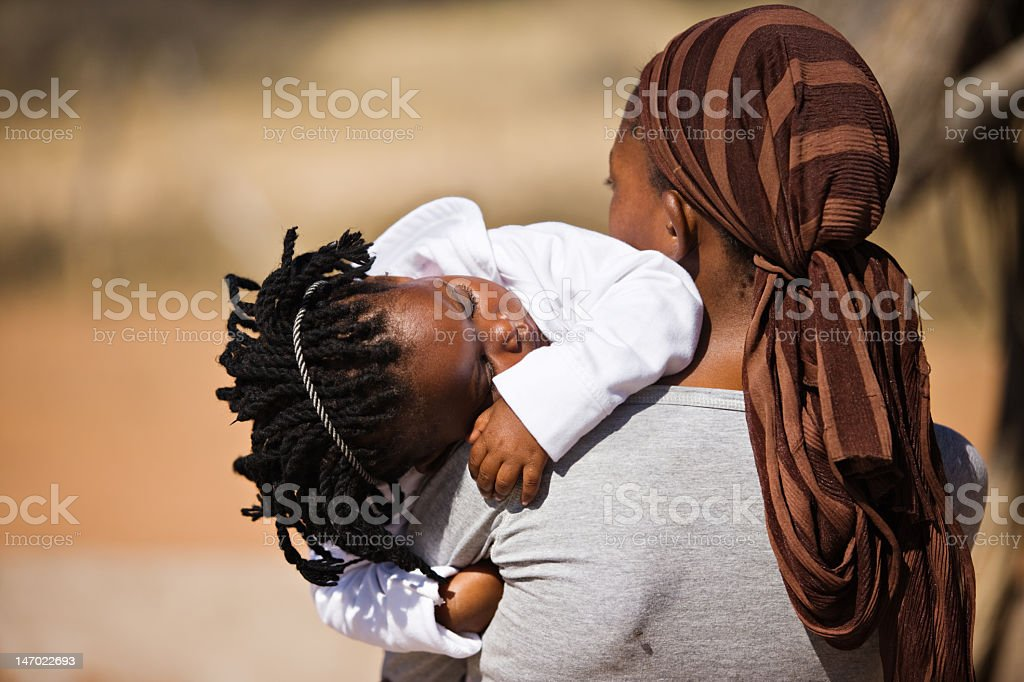 An African woman carrying her sleeping baby girl stock photo