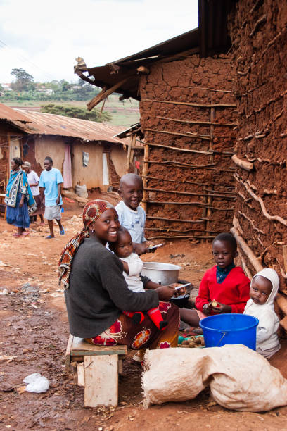 An African Woman Prepares food with her Children stock photo