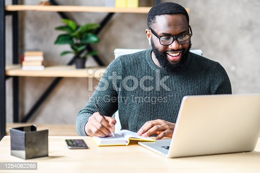 Cheerful African-American male student or worker in glasses is watching online lectures or webinars and writing notes in a notebook