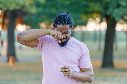 Man of African-American Ethnicity is Rubbing his Eyes Due to Problems with Sight in the Public Park.