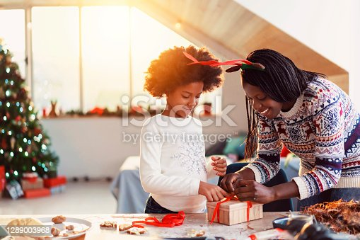 An African-American ethnicity mother and daughter wrapping Christmas presents together.