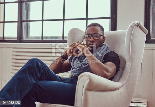 istock An African-American student sits on a chair in a room. 944283120