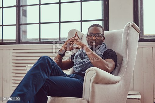 istock An African-American student sits on a chair in a room. 944301190