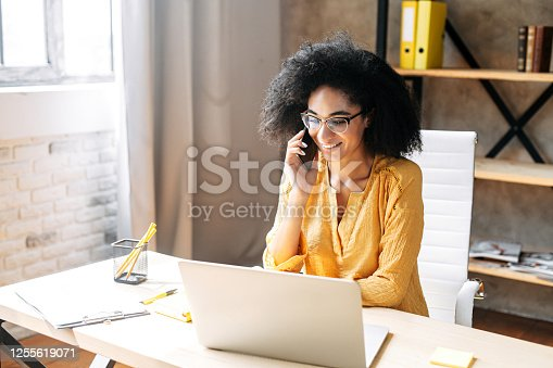 Charming biracial young woman in eyeglasses talks on the smartphone while working with a laptop in modern office