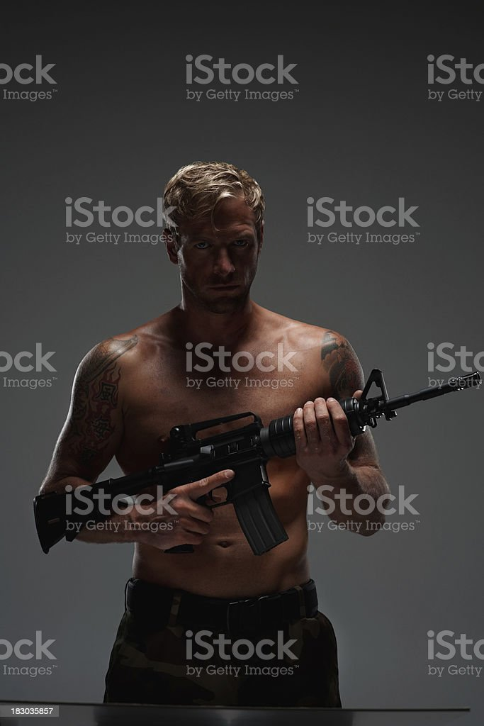 An aggressive young man holding M16 assault rifle - copyspace royalty-free stock photo