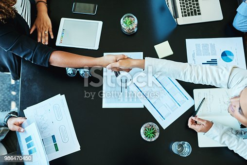 Shot of businesspeople shaking hands during a meeting in an office