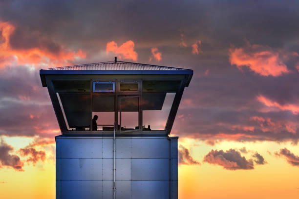An air traffic control tower with the silhouette of male traffic controller, cloudy weather, Iceland. stock photo