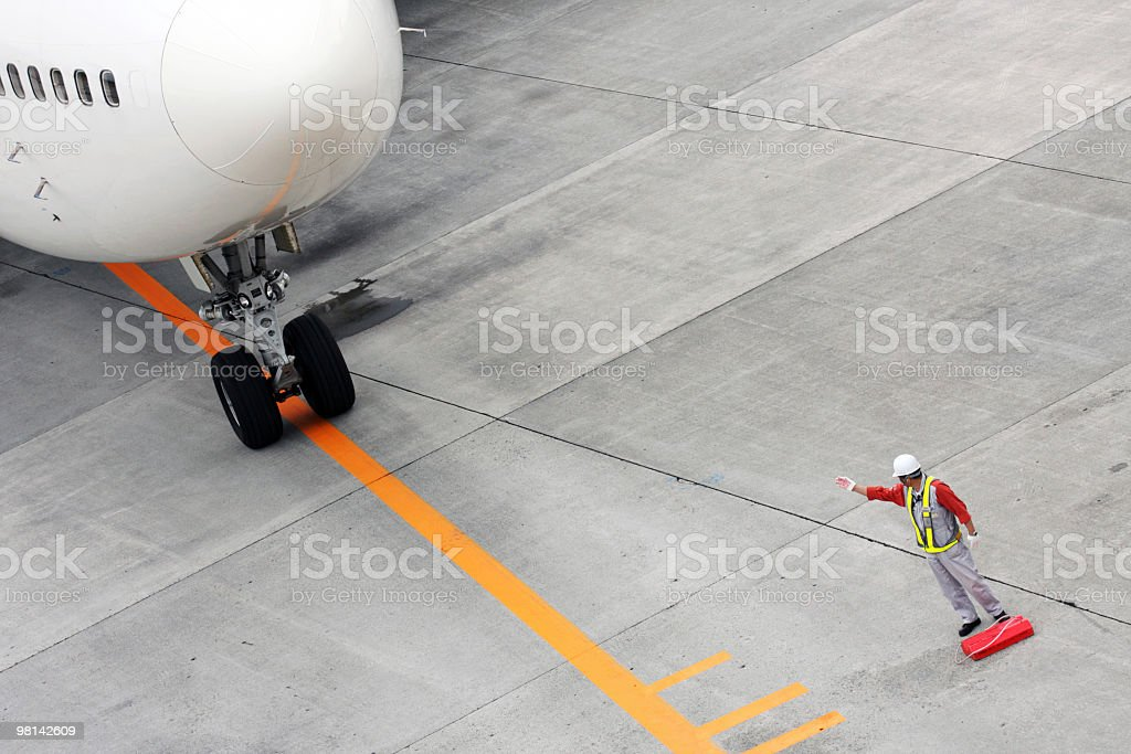 An airfield worker signaling a plane forward royalty-free stock photo