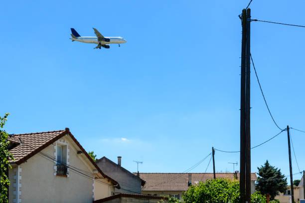 Une avion de ligne en approche d'atterrissage au-dessus d'un quartier résidentiel. - Photo