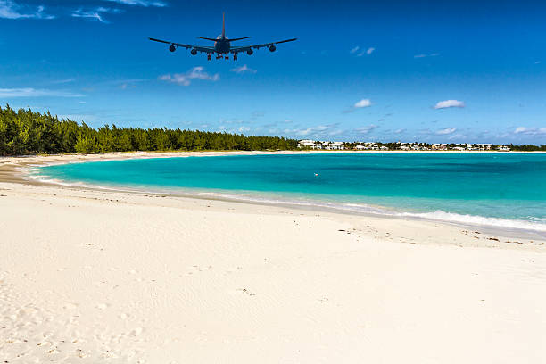 an airplane approaching exuma (bahamas) over emerald bay - exuma foto e immagini stock