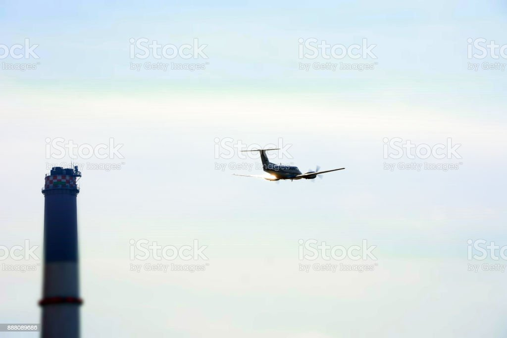 An airplane flew over a chimney stock photo
