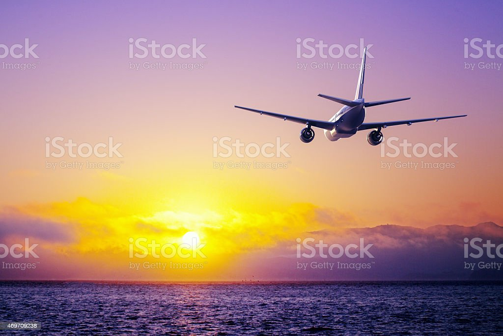 An airplane flying across the air as if chasing the sun stock photo