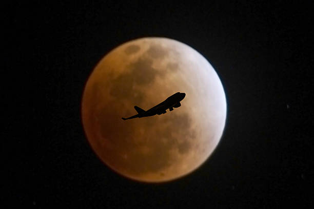an airplane flying at night stock photo