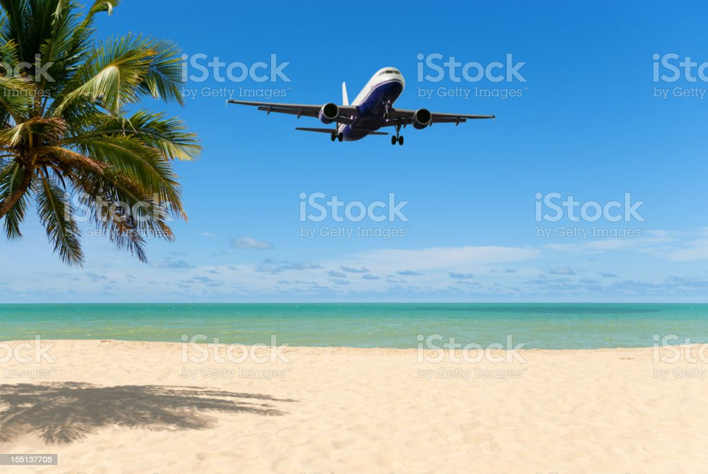 An airplane flying close over a tropical beach stock photo