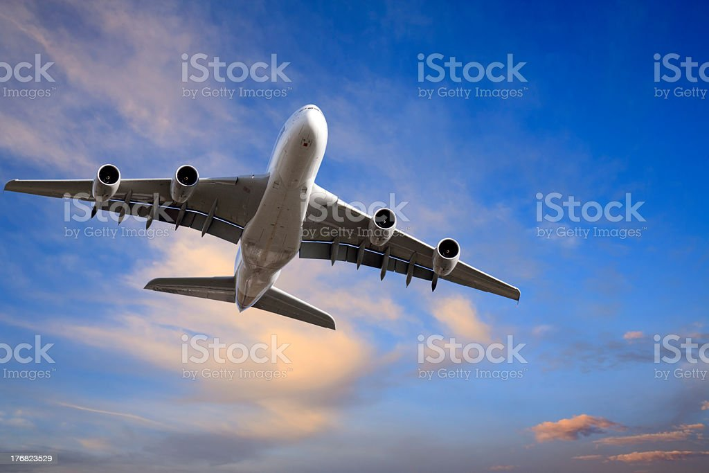 An airplane flying in a cloudy sky royalty-free stock photo