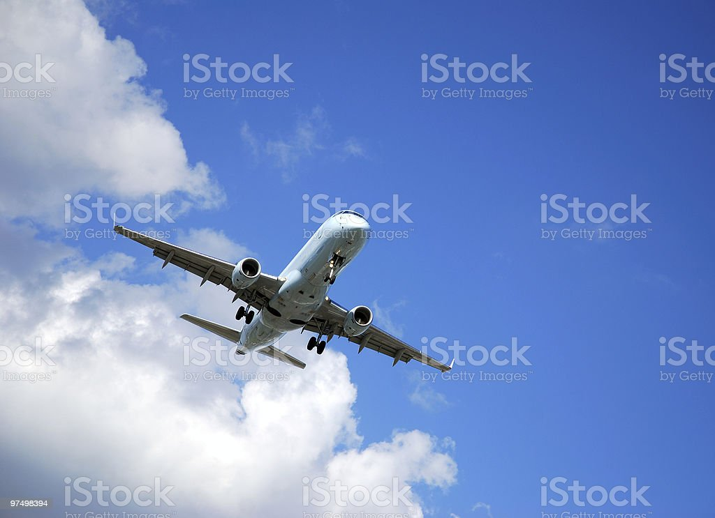An airplane in a landing approach with wheels extended royalty-free stock photo
