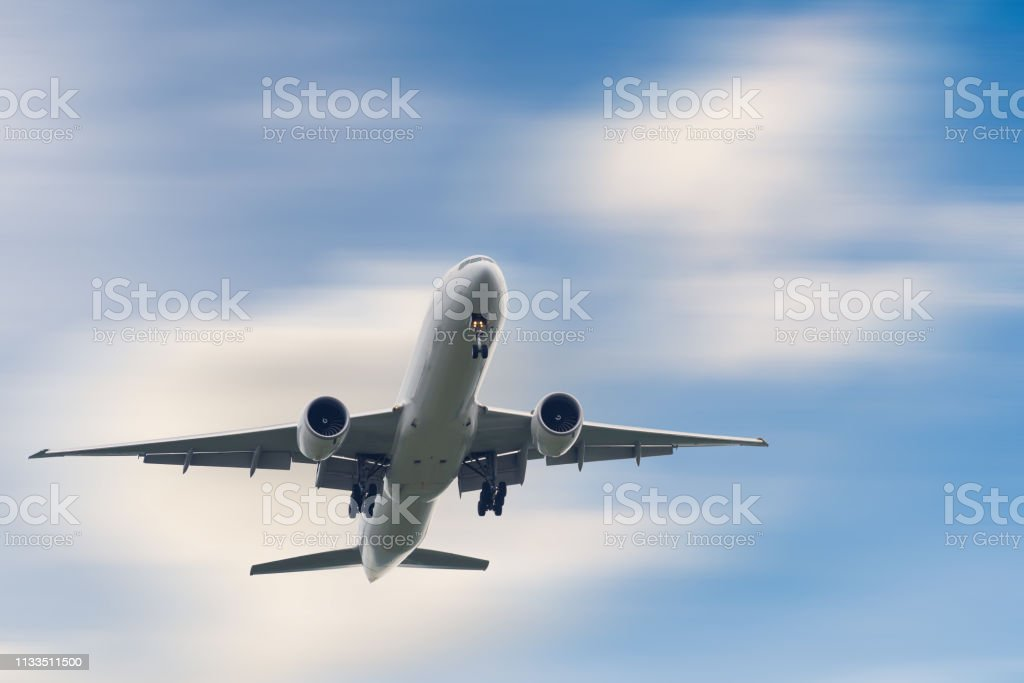 An Airplane is Flying in The Clouds Sky on Vacation Journey, International Aviation and Passengers Transportation, Holiday Trip and Traveling Tourist Concept. stock photo