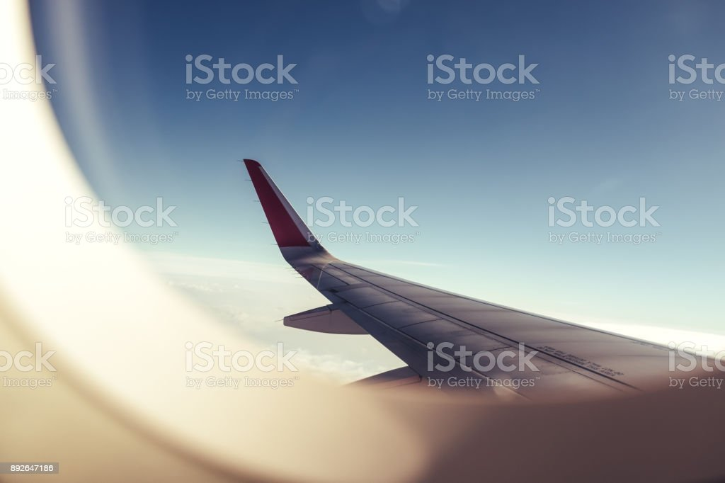 An airplane wing through airplane window with blue sky background stock photo