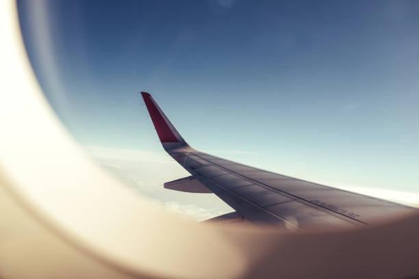 푸른 하늘 배경으로 비행기 창을 통해 비행기 날개 - 항공기 날개 뉴스 사진 이미지