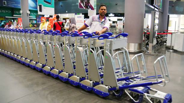 An airport crew pushes a train of luggage trolleys at the Kuala Lumpur International Airport. Kuala Lumpur, Malaysia- March 2018: An airport crew pushes a train of luggage trolleys at the Kuala Lumpur International Airport. kuala lumpur airport stock pictures, royalty-free photos & images