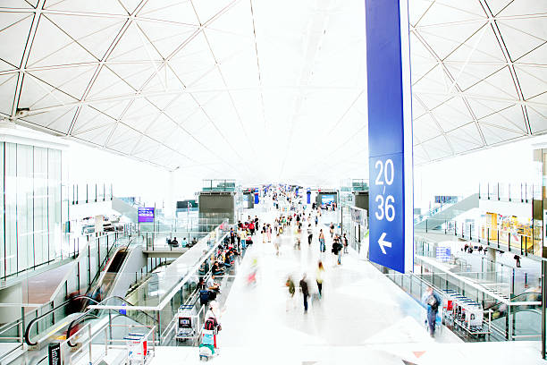 An airport interior, people travelling, motion blurred and high key stock photo