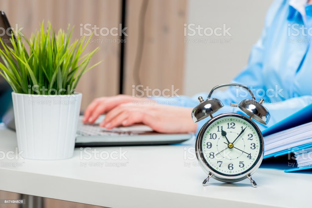An alarm clock on the desk in the office and an accountant out of focus stock photo