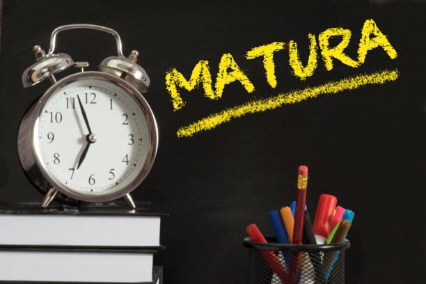 an alarm clock, school books and school board with the word baccalaureate in poland - esame maturità foto e immagini stock