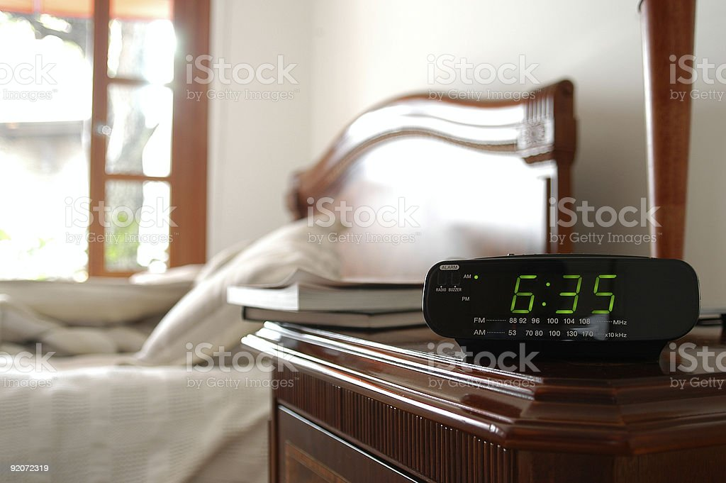 An alarm clock with time of 635 over a blurred bed stock photo
