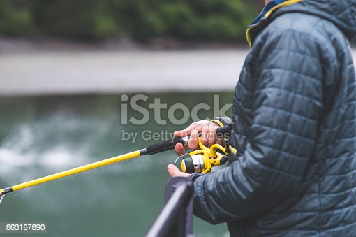istock An Alaska fisherman holds his rod out over the water. 863167890