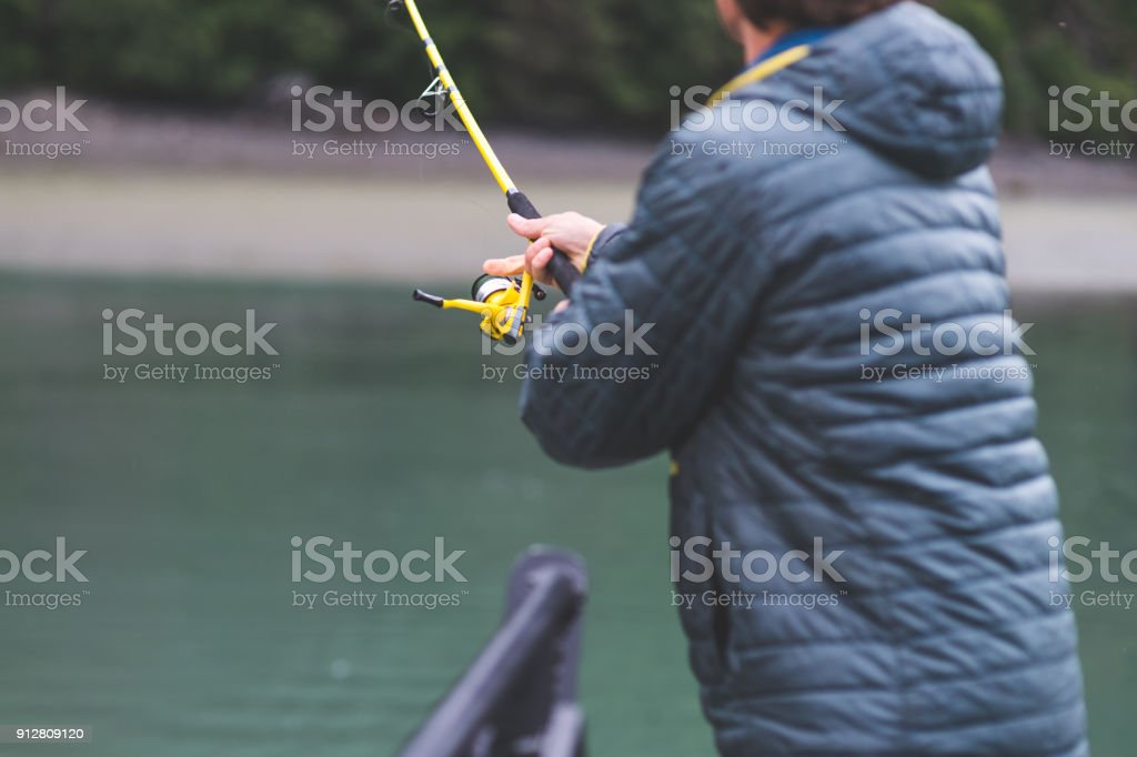 An Alaska fisherman holds his rod out over the water. stock photo