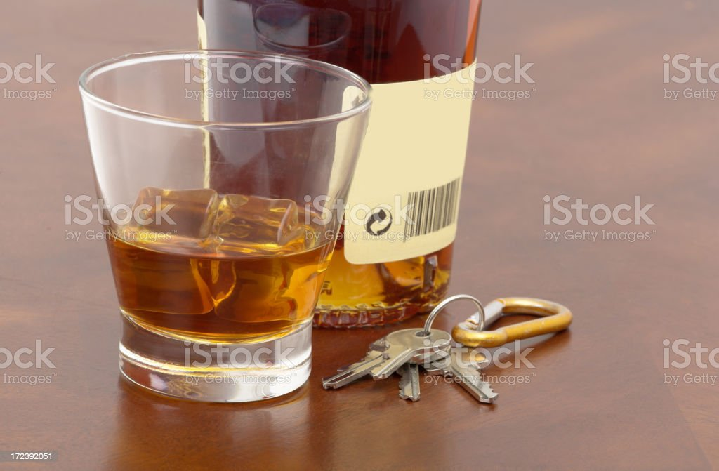 An alcohol drink in a glass alongside the bottle and keys royalty-free stock photo